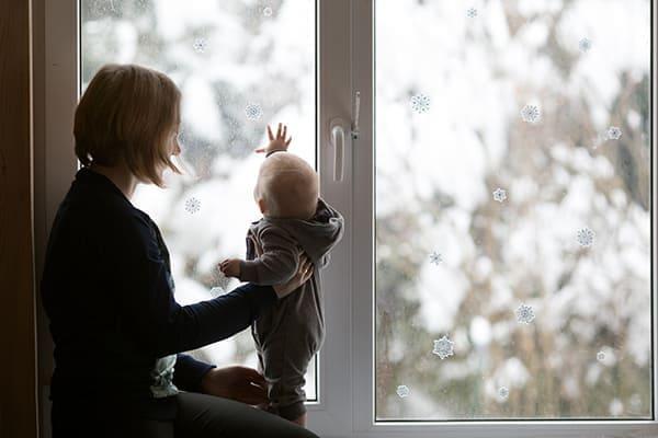 Frau hält kleines Kind das vor dem Fenster steht.